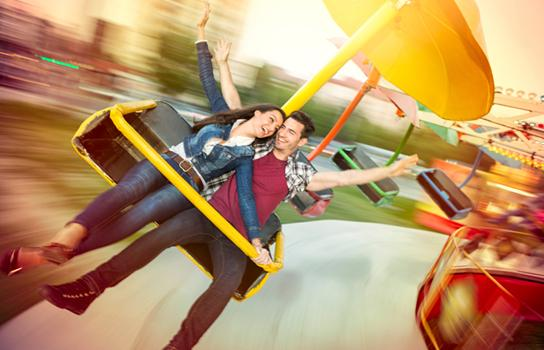 Couple on a theme park ride saving on tickets with AAA