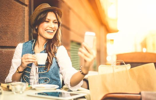 Woman with shopping bags looking at her phone and drinking coffee at an outdoor cafe