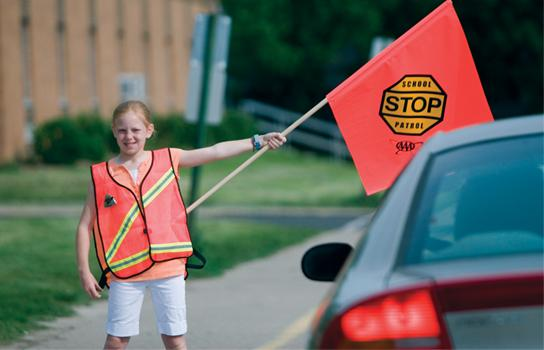 School Patroller in crosswalk stopping a car with patrol flag