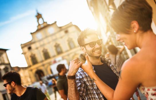 Travelers enjoying discounts dancing in European city