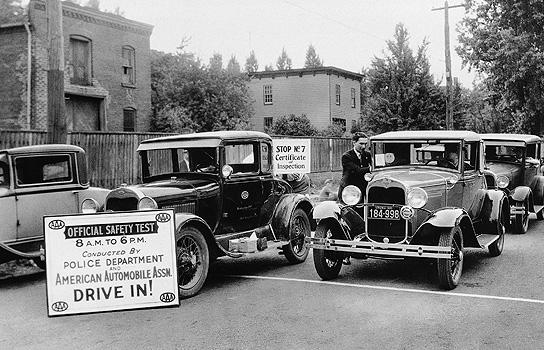Historical photo of automobiles lined up for a safety inspection sponsored by local law enforcement and AAA