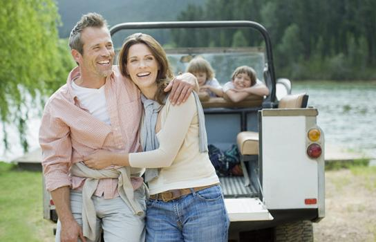 Husband and wife embracing with children laughing in a sport utility vehicle behind them by a lake