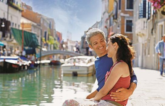 Couple sitting by canal in Europe