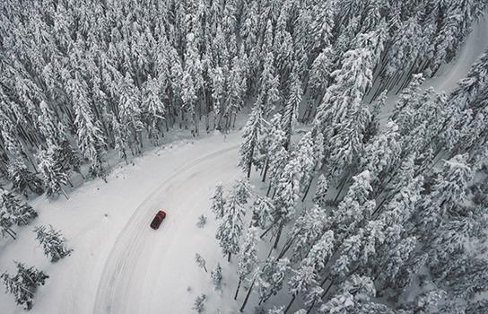 Tips for Safe Winter Driving - car on a snow-covered forest road