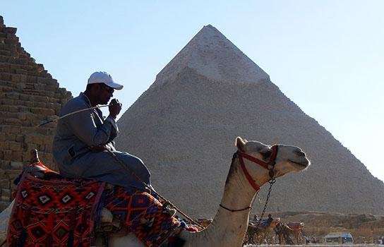 Egyptian on a camel by the pyramids of Giza