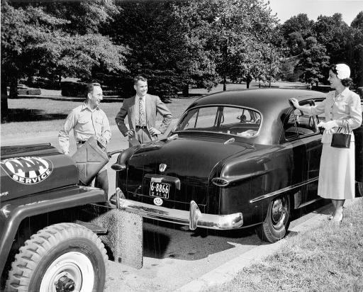 Historical photo of AAA technicians speaking with a member by her vehicle