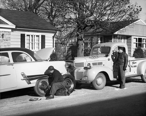 Historical photo of a repair technician servicing a vehicle in a neighborhood
