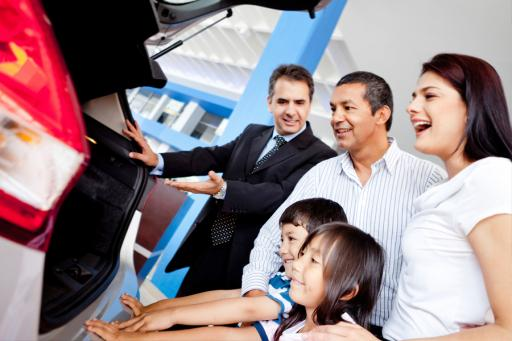 Salesperson with a family at a dealership looking at a car