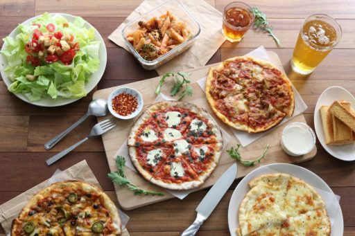salad and pizzas with drinks spread out on a table