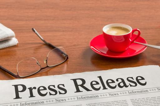 Press Release sitting on a table with reading glasses and a cup of coffee