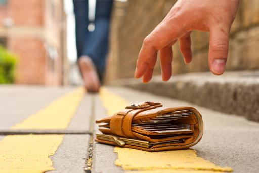 Someone's hand picking up a lost wallet on the ground