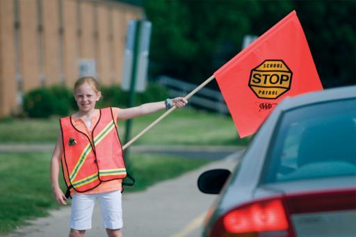 School Safety Patroller in crosswalk stoping a car with patrol flag