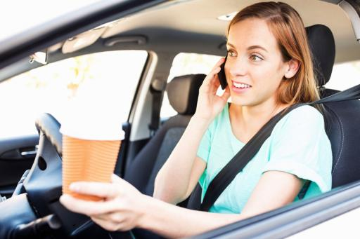 Woman driving distracted with coffee and cell phone