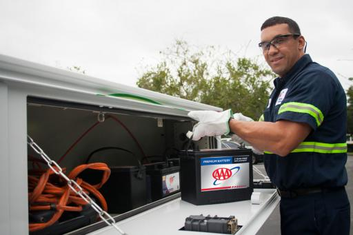 AAA technician unloading a car battery from tow truck