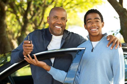 Father handing car keys to son by their car