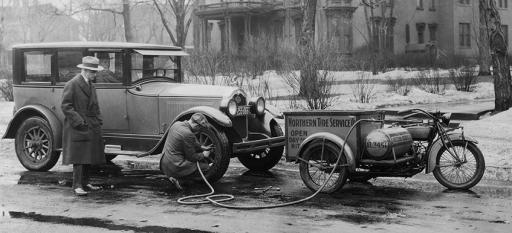 Historical photo of roadside assistance provider fixing a flat tire